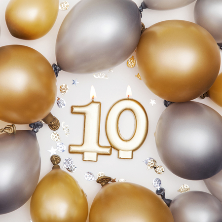 Birthday celebration number 10 candle with gold and silver balloons