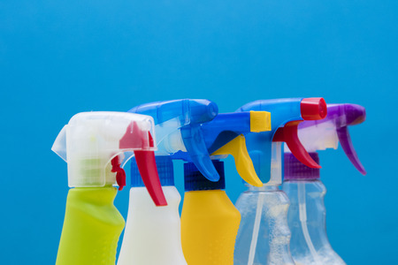 Cleaning spray bottle products on a bright blue background