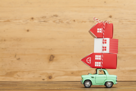 Toy car carrying a stack of houses. Moving house concept Stockfoto
