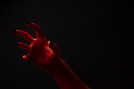 93925731 red devil creepy halloween hand on a black background