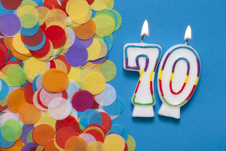 Number 70 celebration candle with party confetti