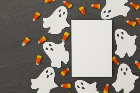 Halloween background with ghosts and candy corn on a slate background