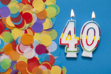 Number 40 celebration candle with party confetti