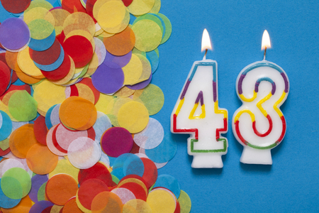 Number 43 celebration candle with party confetti