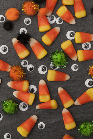Halloween candy corn sweets and googly eyes background