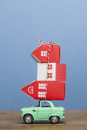 LONDON, UK - JANUARY 19th 2018: A toy oy car carrying a stack of houses against a blue background. Moving house concept