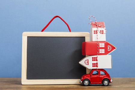 LONDON, UK - JANUARY 19th 2018: A toy oy car carrying a stack of houses against a blank blackboard. Moving house concept Redactioneel