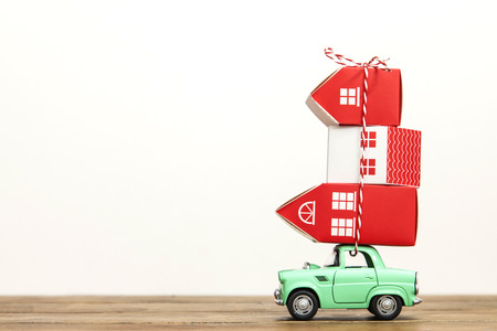 LONDON, UK - JANUARY 19th 2018: A toy oy car carrying a stack of houses against a plain white background. Moving house concept