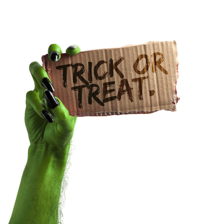 Trick or treat. green witches or zombie monster hand holding a halloween card sign Stock Photo
