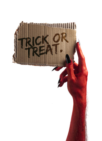Trick or treat. red devil or zombie monster hand holding a halloween sign
