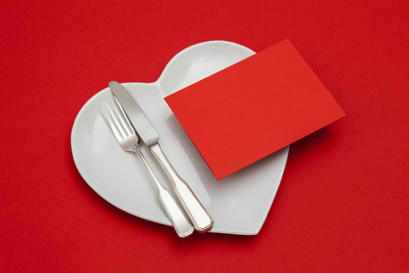 Blank red card on a heart shaped plate with knife and fork