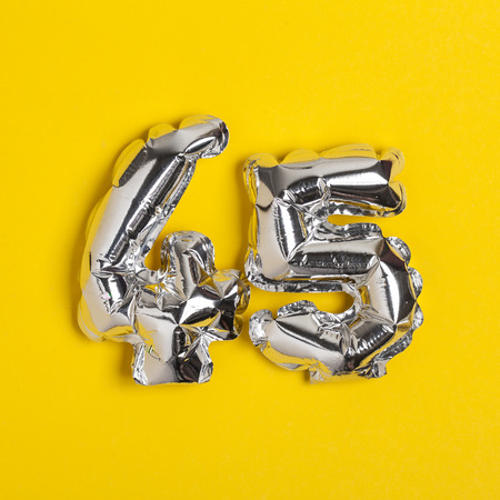 Silver foil number 45 celebration balloon on a bright yellow background