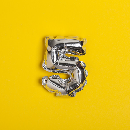 Silver foil number 5 celebration balloon on a bright yellow background Archivio Fotografico