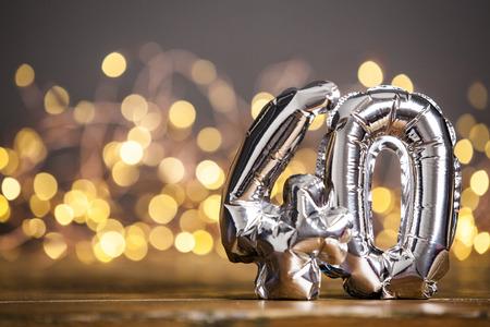 Silver number 40 celebration foil balloon against blurred light background