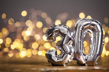 Silver number 30 celebration foil balloon against blurred light background