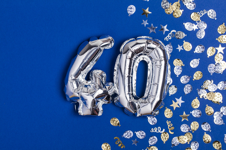 Silver foil number 40 balloon on a blue background with glitter gonfetti Stok Fotoğraf