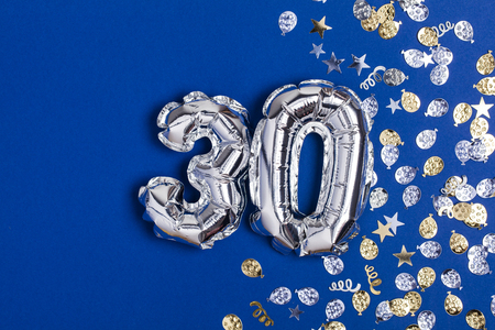 Silver foil number 30 balloon on a blue background with glitter gonfetti