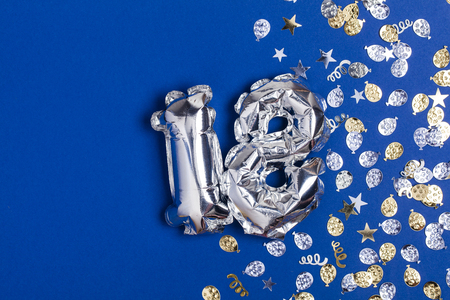 Silver foil number 18 balloon on a blue background with glitter gonfetti