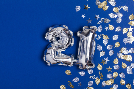 Silver foil number 21 balloon on a blue background with glitter gonfetti