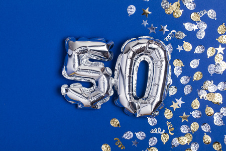 Silver foil number 50 balloon on a blue background with glitter gonfetti Foto de archivo