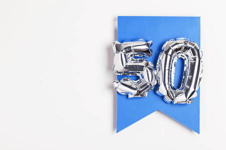 Number 50 silver balloon celebration number on a blue banner Stock Photo