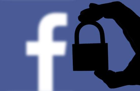LONDON, UK - FEBRUARY 5th 2018: Facebook security issues. Silhouette of a hand holding a padlock infront of the facebook logo 에디토리얼
