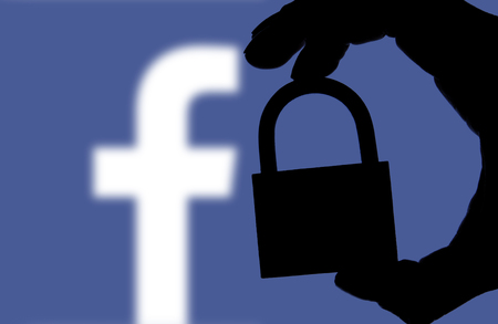 LONDON, UK - FEBRUARY 5th 2018: Facebook security issues. Silhouette of a hand holding a padlock infront of the facebook logo Redactioneel