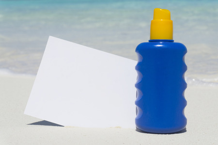 Bottle of sun lotion suncream protection and blank note on a tropical beach