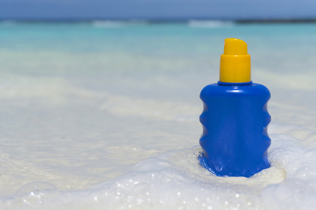 Bottle of sun lotion suncream protection on a tropical beach