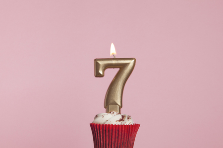 Number 7 gold candle in a cupcake against a pastel pink background