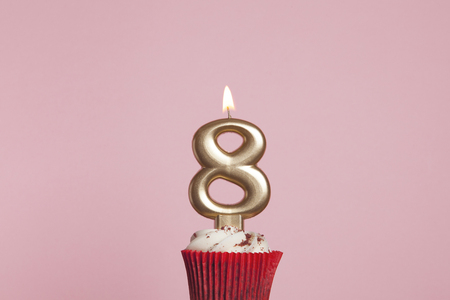 Number 8 gold candle in a cupcake against a pastel pink background Standard-Bild