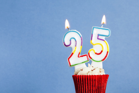 Number 25 birthday candle in a cupcake against a blue background Banco de Imagens - 95834179