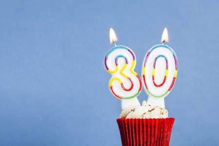 Number 30 birthday candle in a cupcake against a blue background Imagens