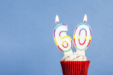 Number 60 birthday candle in a cupcake against a blue background Reklamní fotografie