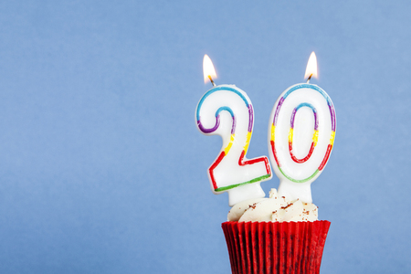 Number 20 birthday candle in a cupcake against a blue background