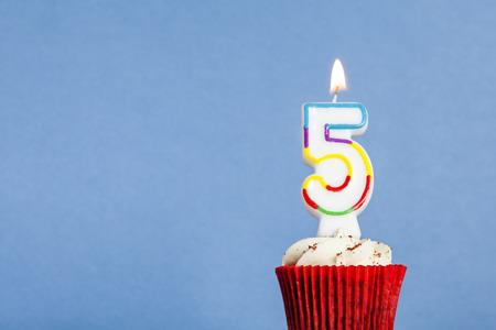 Number 5 birthday candle in a cupcake against a blue background