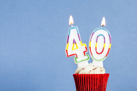 Number 40 birthday candle in a cupcake against a blue background