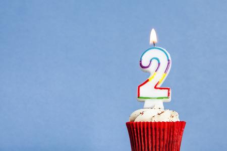 Bougie d'anniversaire numéro 2 dans un petit gâteau sur un fond bleu Banque d'images