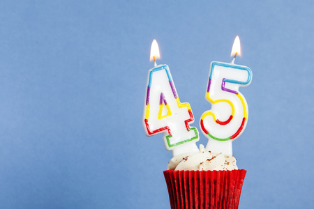 Number 45 birthday candle in a cupcake against a blue background