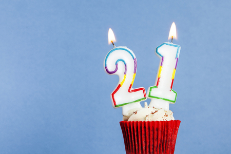 Number 21 birthday candle in a cupcake against a blue background Stock fotó