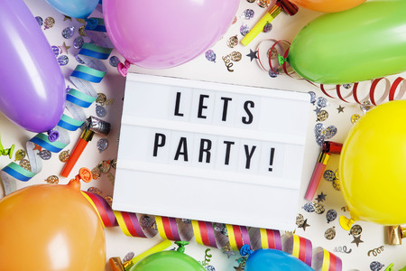 Party celebration background with lets party message on a lightbox Stock Photo
