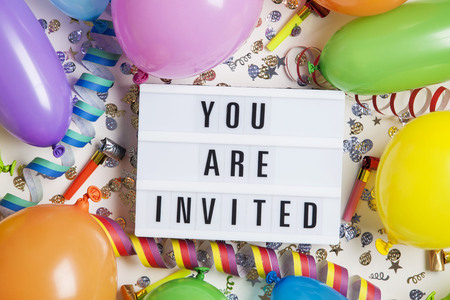Party celebration background with you are invited message on a lightbox Stock Photo