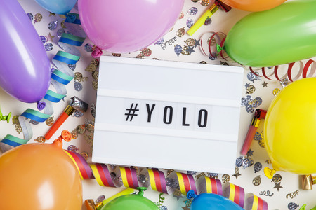 Party celebration background with yolo message on a lightbox Stock Photo