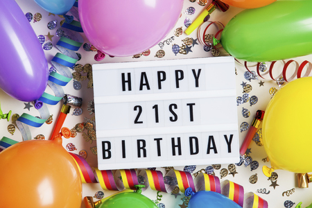 Happy 21st birthday celebration message on a lightbox with balloons and confetti Stock Photo