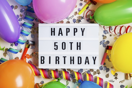 Happy 50th birthday celebration message on a lightbox with balloons and confetti