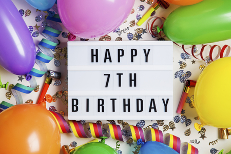 Happy 7th birthday celebration message on a lightbox with balloons and confetti Stock Photo
