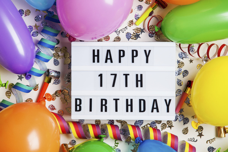 Happy 17th birthday celebration message on a lightbox with balloons and confetti Stock Photo
