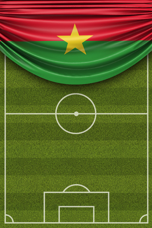 Burkina Faso country flag draped over a football soccer pitch. 3D Rendering