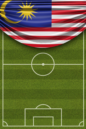 Malaysia country flag draped over a football soccer pitch. 3D Rendering