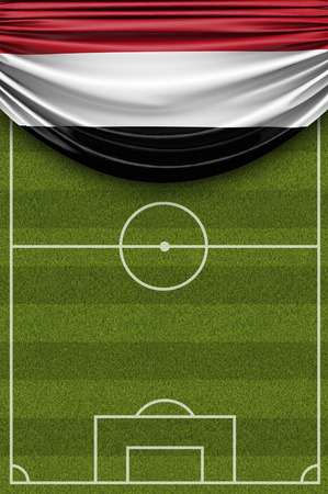 Yemen country flag draped over a football soccer pitch. 3D Rendering